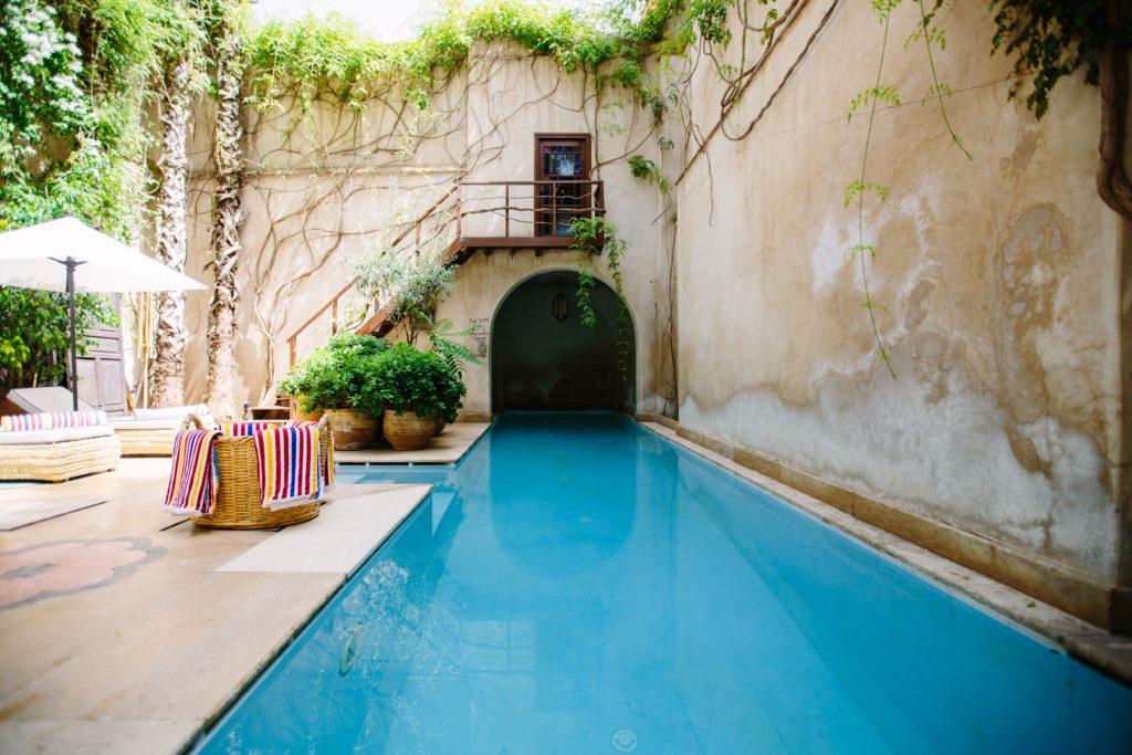 vista interior de hotel boutique con piscina, muebles y plantas decorativas alrededor