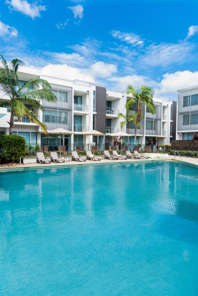 """""""hotel con sillas y palmera rodeando una piscina"""""""