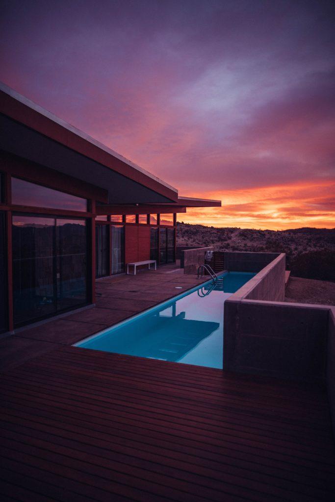 vista de edificio de lujo con piscina y terraza mirando el atardecer