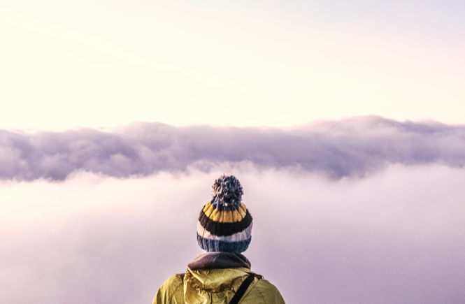 silueta de hombre con chaqueta y gorro viendo hacia las nubes