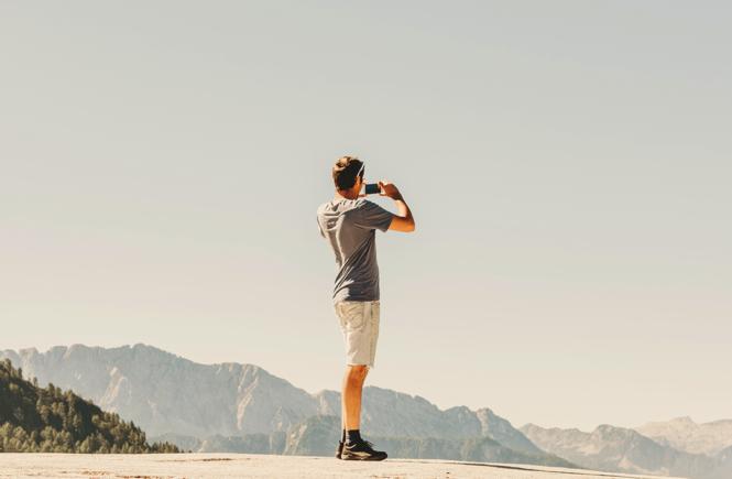 viajero tomando una fotografia encima de una montaña