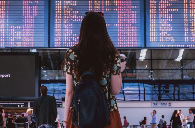 Mujer de pie frente a tablero de vuelos en un aeropuerto
